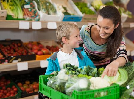 Cheerful mother with little boy buying broccoli at store