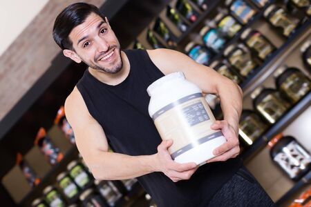 Happy man holding  sport nutrition products in store