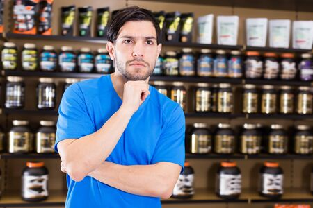 Adult sportman standing near shelves with sport nutrition in shop