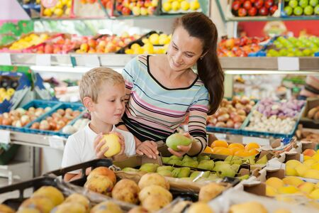 Boy with his mother choosing fresh pears and apples at fruit department of supermarket