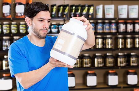 Attractive sportman choosing different sport nutrition products in sport food store