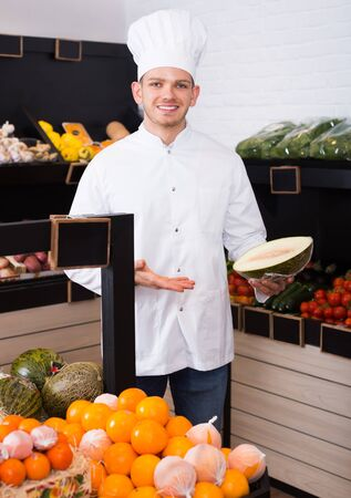 Male chef looking for fresh fruits in grocery shop