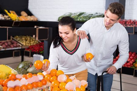 Positive couple of buyers examining various fruits in grocery shop
