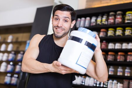 Attractive sport man vendee showing   sport nutrition products in store