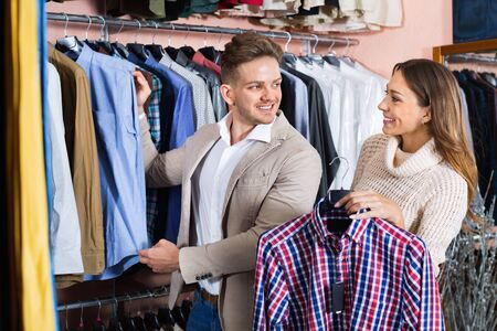 Young loving happy  positive couple deciding on new shirt in men's cloths store