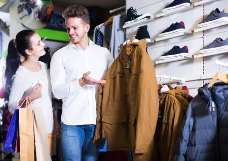 happy european loving couple deciding on warm suit in sports store