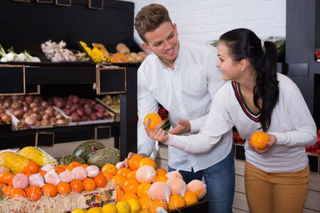 Loving couple deciding on fruits in grocery shop 스톡 콘텐츠