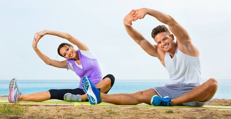 Young glad cheerful couple training yoga poses sitting on beach on sunny morning Stockfoto