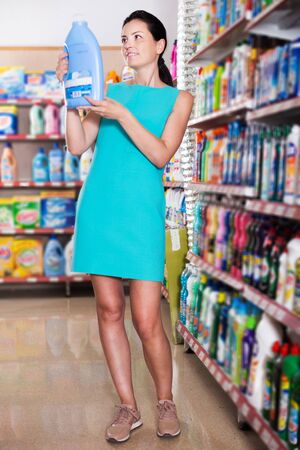 Adult woman choosing detergent for washing at the supermarket