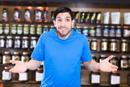 adult muscular man  standing near shelves with sport nutrition in shop