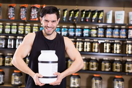 Attractive sport man seller showing  different sport nutrition products in store