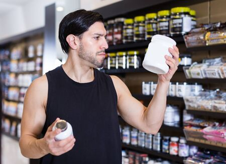Serious muscular guy attentevely looking sport nutrition products in sport shop