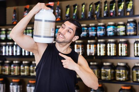 Attractive athletic positive smiling man on shoulder  sport food products in store, showing his power Stockfoto
