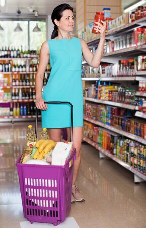 Adult female choosing jar of tomato paste in the food shop with purchases 写真素材 - 129974835