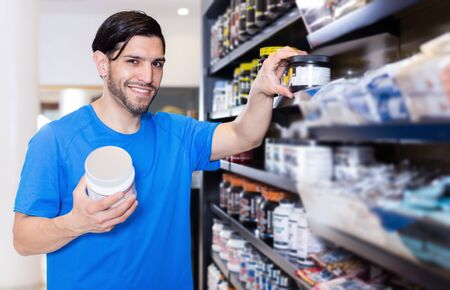 Positive young sport man looking different sport nutrition products in store