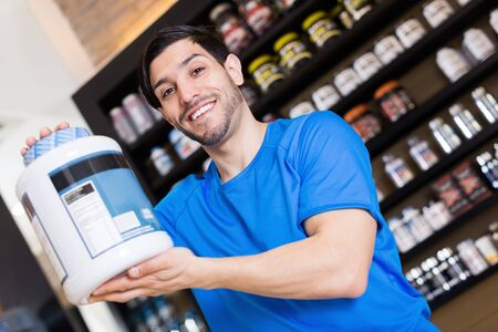 Positive muscular male seller showing big pot of dietary supplements  in sport shop