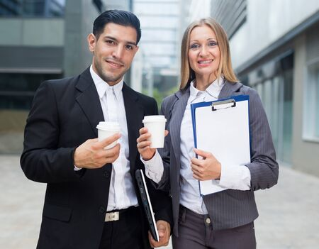 Portrait of couple who are standing with folder and coffee near the office.