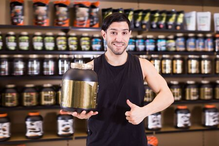 Attractive sport man with big pot of sport nutrition products holding thumb up  in store