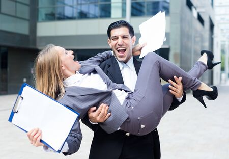 Businessman is carry his partner woman on hands because they are signed successful contract outdoors near office. Stock fotó