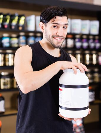 Active muscular smiling cheerful man showing his power and holding pot of  sport nutrition in shop