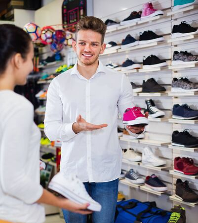 Young  glad friendly  man seller assisting girl in choosing sneakers in sports store Stok Fotoğraf