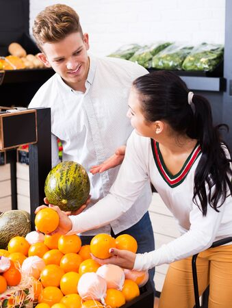 Young cheerful couple choosing fruits in grocery store 写真素材 - 129974879