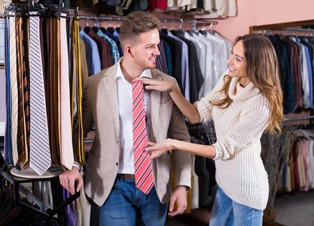 couple examining various ties in men's cloths store Фото со стока