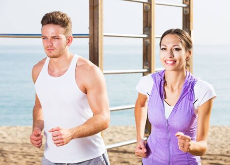 Young smiling man and woman running together on beach on sunny morning