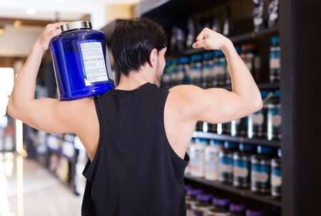 Back view of athletic adult sportman holding on shoulder sport nutrition  in shop