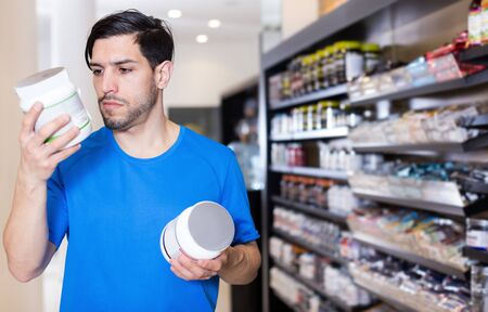 Attractive sportsmen choosing attentively sport nutrition products in sport  store