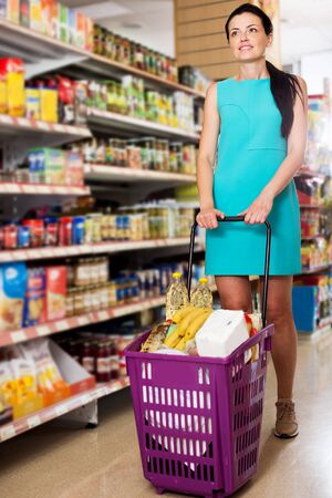 Cheerful woman with shopping cart standing in the modern supermarket