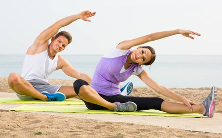 Smiling  woman and guy training on beach by sea in sunny morning Stockfoto