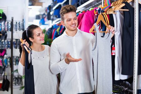 Young smiling  positive couple choosing new sportswear in sports store Banco de Imagens