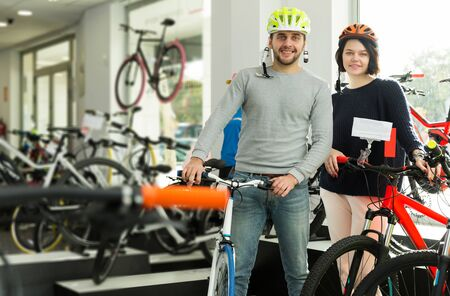 young couple in helmet standing with cycle in the store