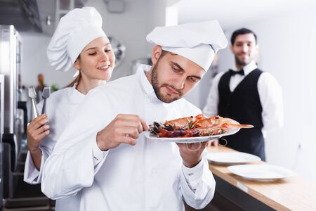 Head chef checking dishes in kitchen of fish restaurant before serving guests