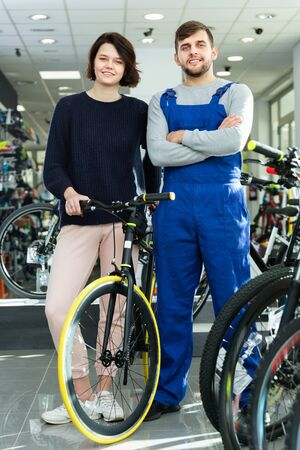 Smiling cheerful  woman and seller standing with bicycle in the store indoors 写真素材