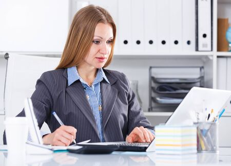 Elegant business woman concentrating on work on laptop in office