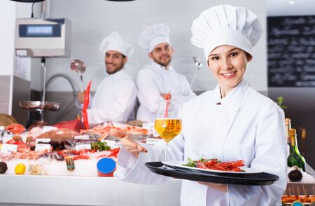 Attractive glad cheerful positive female chef with serving tray, offering dishes in fish restaurant
