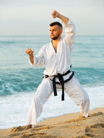 Male 30-40 years old training the Shiko-dachi stance on the beach near the sea.