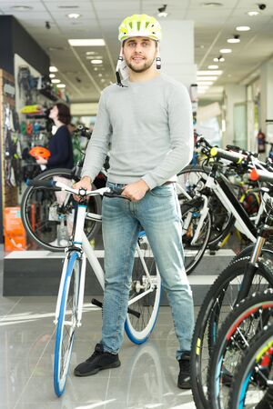 male in helmet standing near the bicycle in the store
