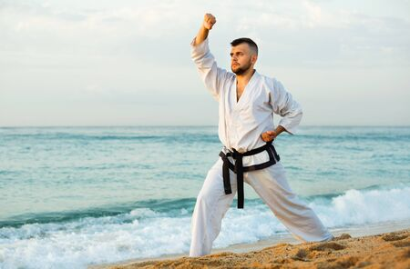 Glad cheerful young guy doing karate poses at sunset sea shore