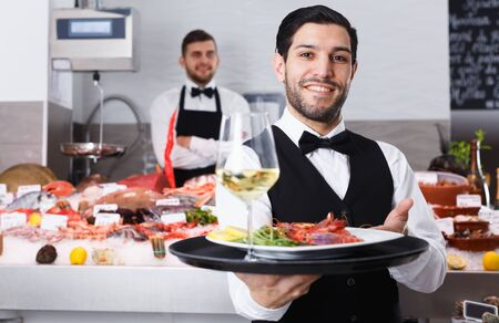Handsome bearded waiter standing with serving tray in fish restaurant