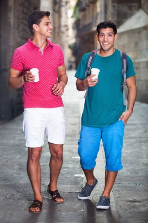 Happy cheerful  smiling men friends are drinking coffee in time walking in city.