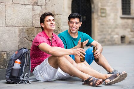 glad male fans are drinking beer and talking about football outdoor in Barcelona outdoors