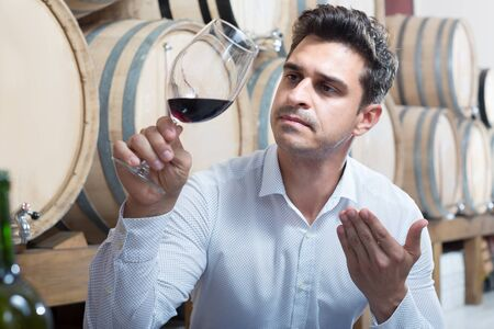 Positive male expert holding glass of red wine in shop with woods and tasting it
