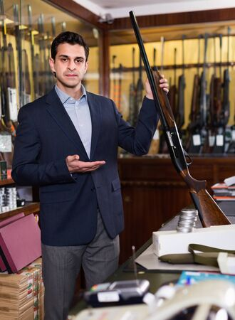 Handsome positive glad adult male in hunting shop with rifle in hands