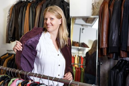 Positive young woman trying on clothes in leather outerwear shop