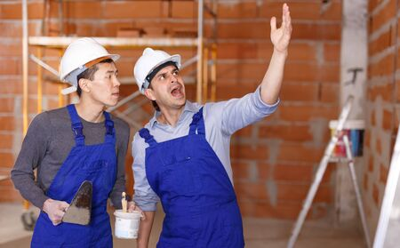 Senior worker criticizing builder for poor quality of finishing work at private house