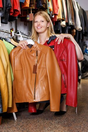smiling young blonde woman choosing leather jacket on racks in clothes store Stockfoto