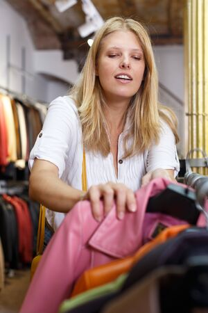 Attractive young blonde choosing leather jacket on racks in clothes store Stockfoto - 130048964